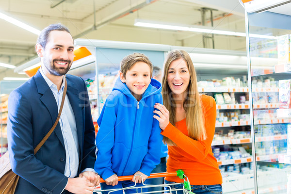 Family with shopping cart in grocery store Stock photo © Kzenon