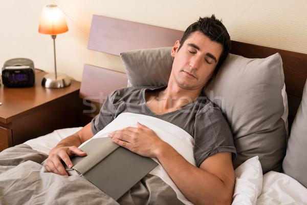 Młody człowiek objętych czytania książki bed Zdjęcia stock © Kzenon