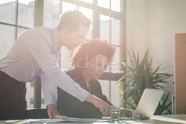 Skilled business man helping his colleague in the office Stock photo © Kzenon