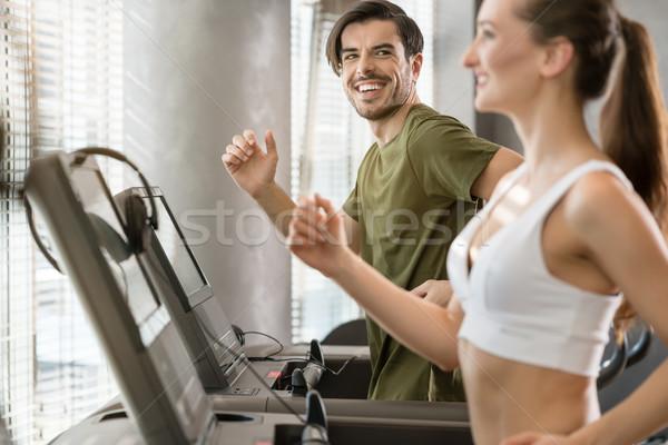 Határozott fiatalember mosolyog fut futópad időszak Stock fotó © Kzenon