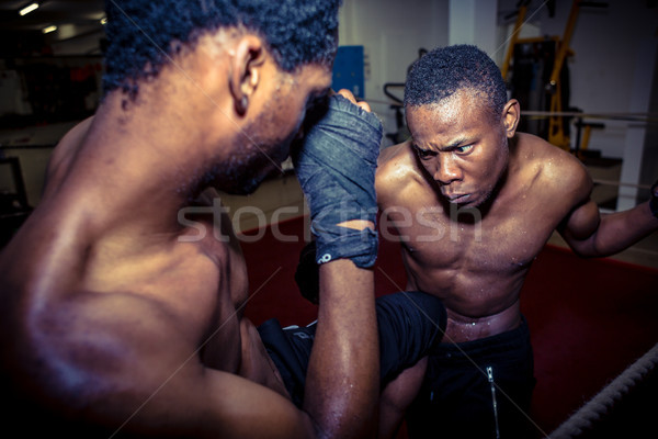 Determined offensive fighter hitting his opponent while practici Stock photo © Kzenon