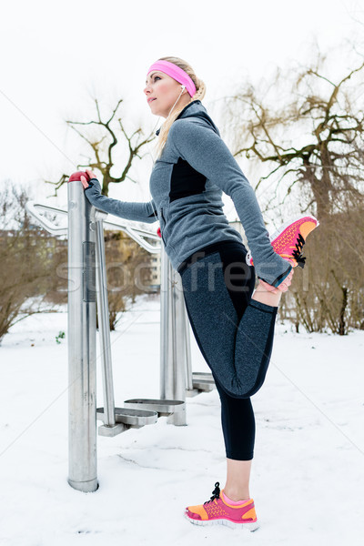Woman stretching her legs for sport on a winter day Stock photo © Kzenon
