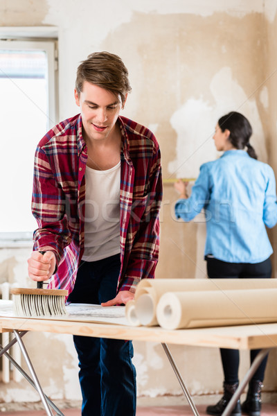 Young man applying adhesive to wallpaper while girlfriend is measuring the wall Stock photo © Kzenon