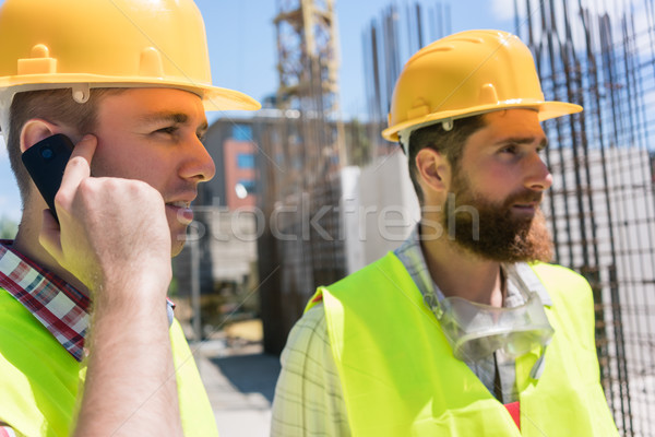 Worker talking on mobile phone during work on a construction site Stock photo © Kzenon
