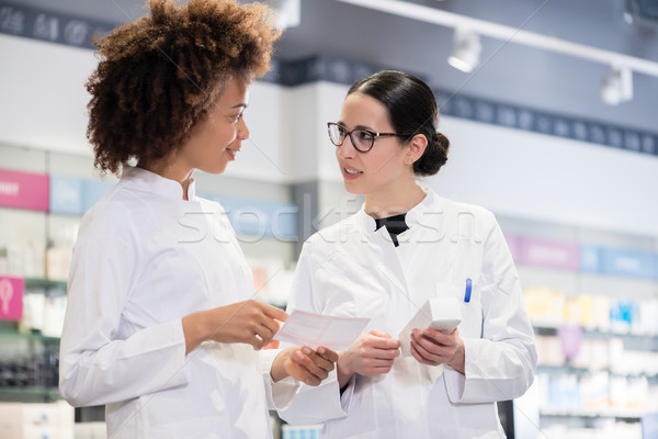 Two pharmacists comparing medicines regarding indications and side effects Stock photo © Kzenon