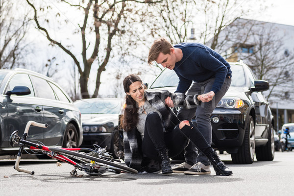 Reliable young man helping an injured woman while waiting for the ambulance Stock photo © Kzenon