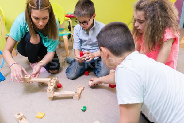 Toegewijd kleuterschool leraar helpen kinderen bouw Stockfoto © Kzenon