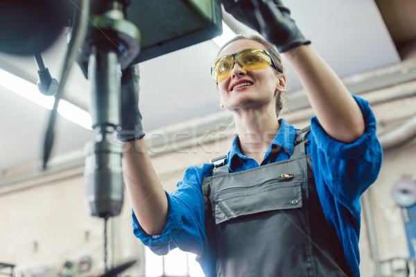 Woman worker in metal workshop using pedestal drill Stock photo © Kzenon