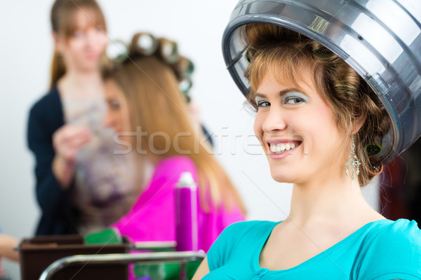 Women at the hairdresser curling hair Stock photo © Kzenon