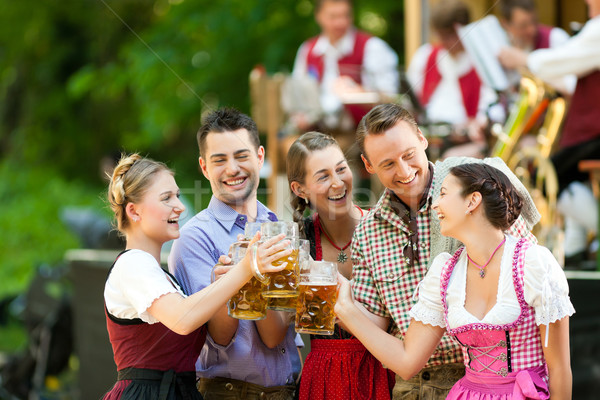 In Beer garden - friends in front of band Stock photo © Kzenon