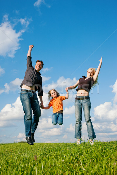 Stock photo: Family jumping on meadow in summer