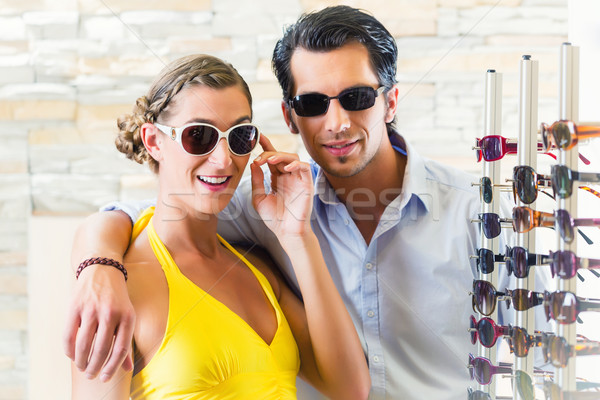 couple at optician or optometrist buying sunglasses Stock photo © Kzenon