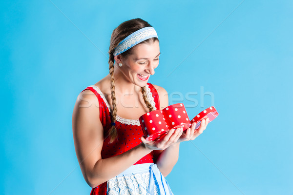 Woman in dirndl dress opening gift or present Stock photo © Kzenon