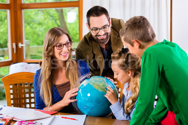 Parents helping daughter with homework assignment Stock photo © Kzenon