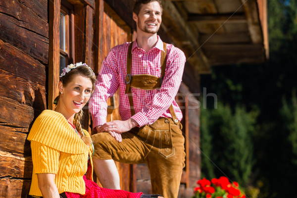 Couple in traditional clothing front of mountain hut Stock photo © Kzenon