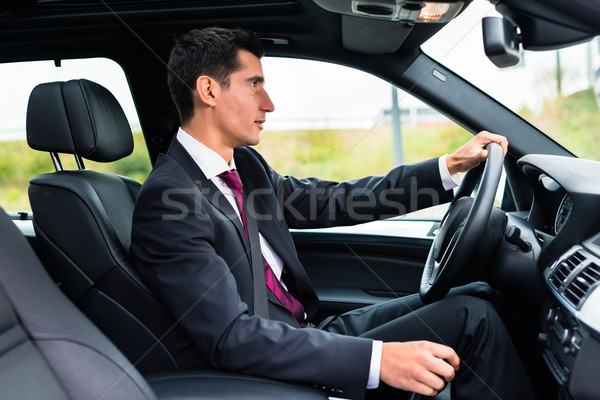 Man driving in his car in business attire Stock photo © Kzenon