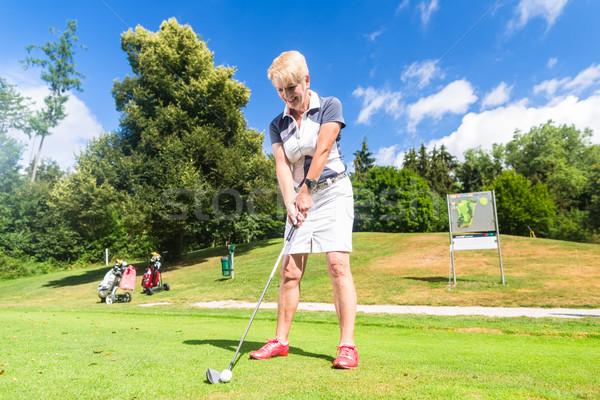 Senior woman doing tee stroke on golf course Stock photo © Kzenon