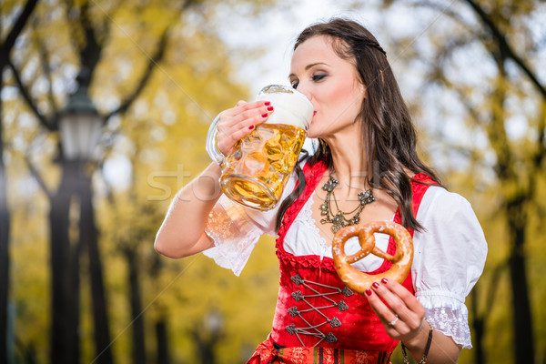 Girl in traditional bavarian Tracht drinking beer out of huge mu Stock photo © Kzenon