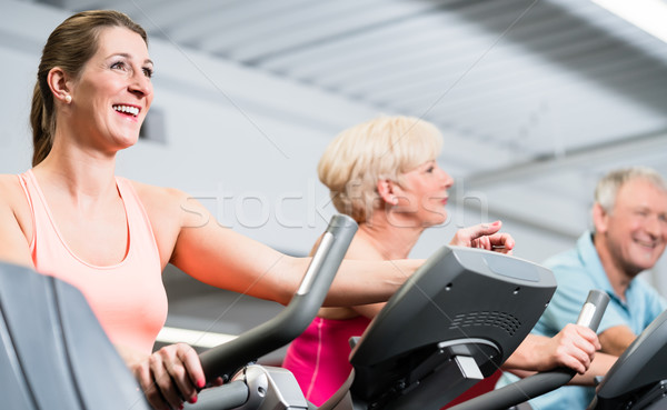 Young woman and senior couple spinning at the gym Stock photo © Kzenon