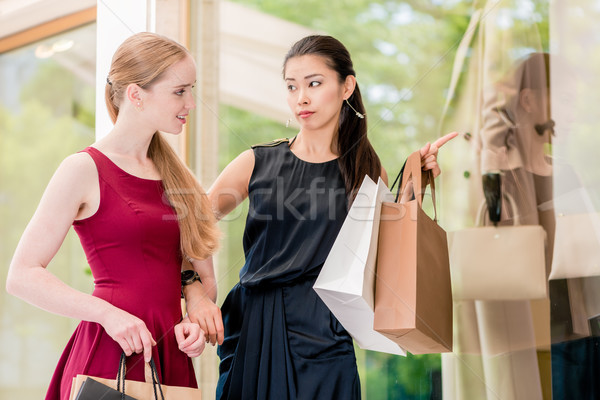 Stock photo: Two female best friends looking at the latest fashion trends whi