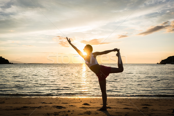 Fit woman practicing on the beach the standing bow pulling pose  Stock photo © Kzenon