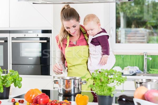 Anne pişirme bebek kol ev mutfak Stok fotoğraf © Kzenon