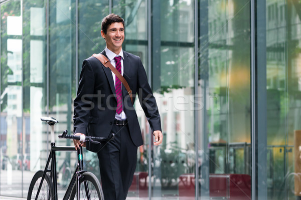 Happy active young man walking to the job after bicycle commutin Stock photo © Kzenon