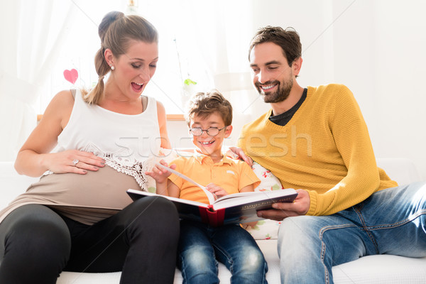 Parents showing their firstborn son pictures in family album Stock photo © Kzenon