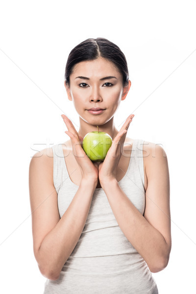 Thoughtful young Asian woman holding a green apple Stock photo © Kzenon