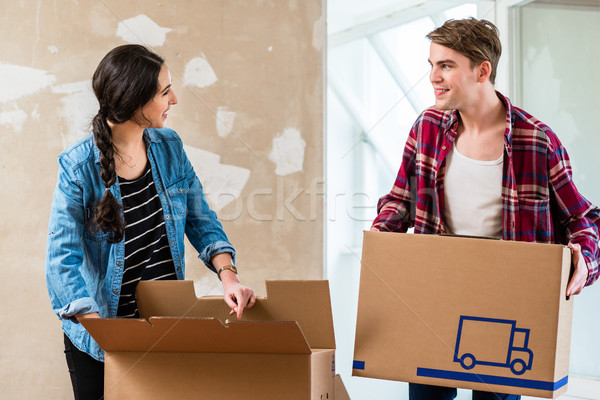 Young man opening a box while moving with his girlfriend into a  Stock photo © Kzenon