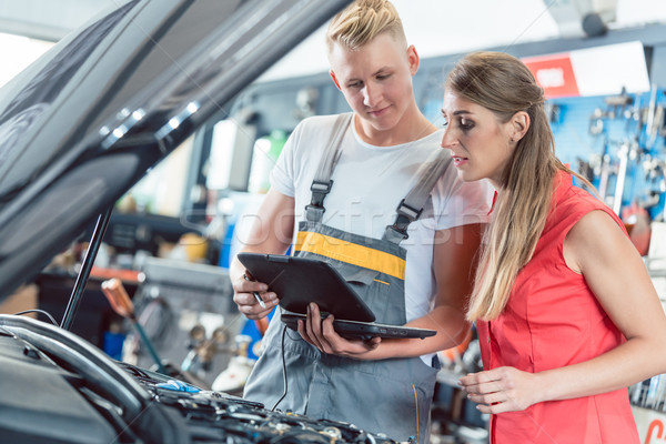 Auto mechanic showing to a customer the engine error codes Stock photo © Kzenon