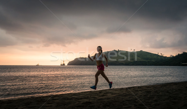 Fit young woman running on the beach during summer vacation in Flores Island Stock photo © Kzenon