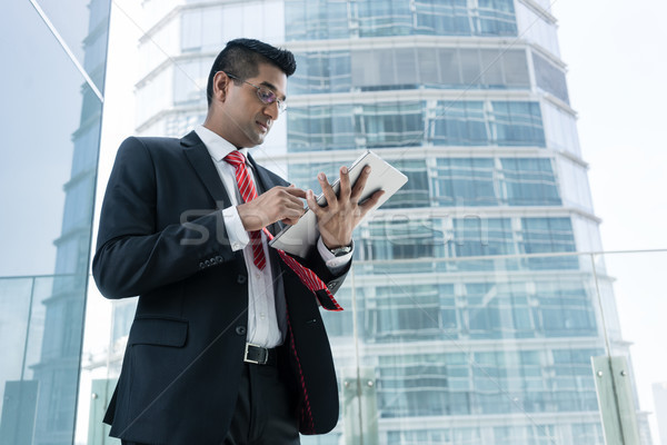 Indian businessman analyzing financial report indoors Stock photo © Kzenon