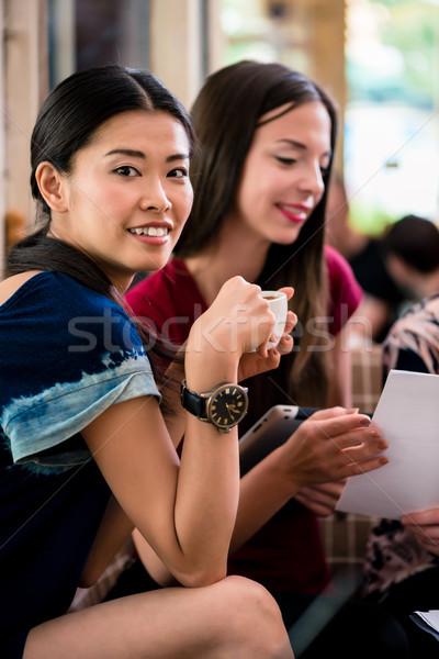 Fiatal nő mutat papírmunka barátok ül együtt Stock fotó © Kzenon