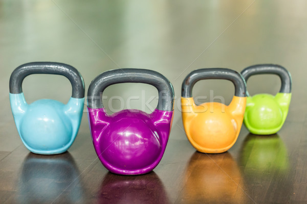 Close-up of four kettlebells of different colors and weights Stock photo © Kzenon