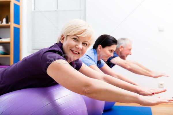 Physio showing senior couple how to use gym ball for exercises Stock photo © Kzenon