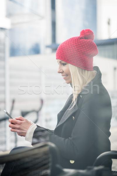 Woman using phone while waiting for a suburban train Stock photo © Kzenon