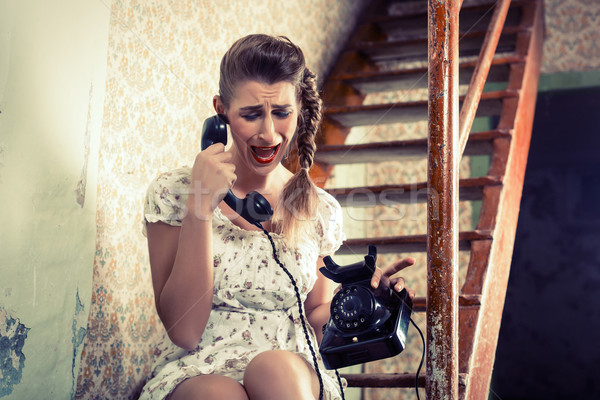Woman sitting on the stairs and crying on the phone Stock photo © Kzenon