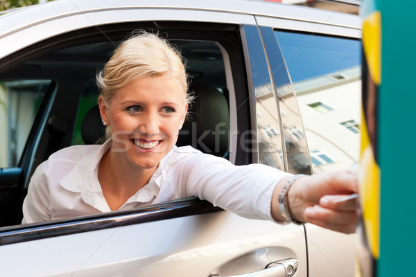 Woman is inserting parking ticket into barrier of garage Stock photo © Kzenon