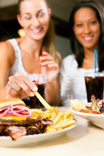 две женщины еды гамбургер питьевой соды один Сток-фото © Kzenon