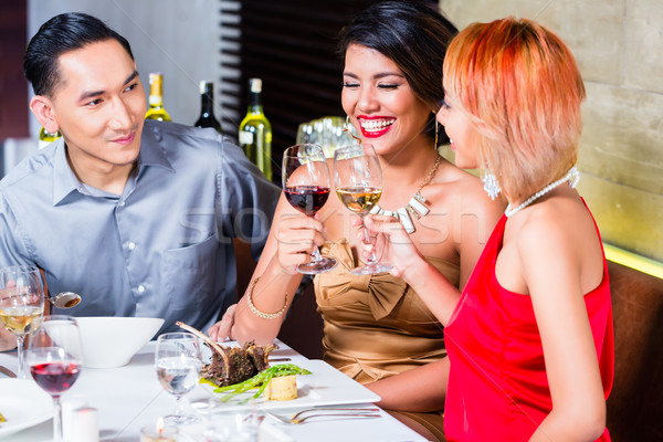 Asian friends dining in fancy restaurant Stock photo © Kzenon