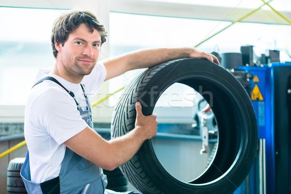 Auto mechanic changing tire in car workshop Stock photo © Kzenon