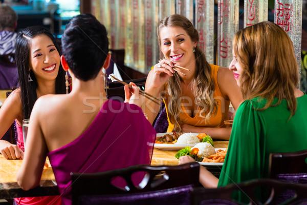 Fiatalok eszik Ázsia étterem étel nők Stock fotó © Kzenon