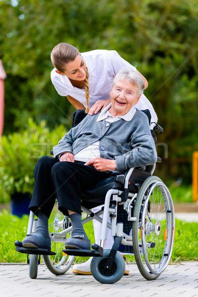 Nurse pushing senior woman in wheelchair on walk Stock photo © Kzenon
