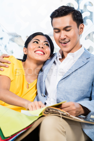 Stock photo: Asian couple buying sofa in furniture store