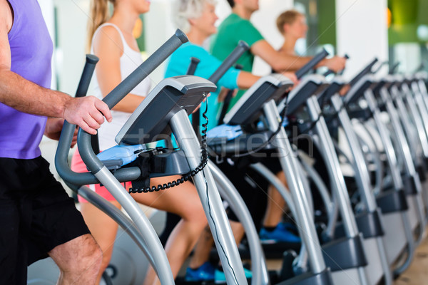 Group with senior people on elliptical trainer in gym Stock photo © Kzenon