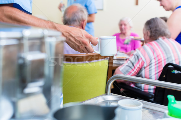 Nurse serving food in nursing home Stock photo © Kzenon