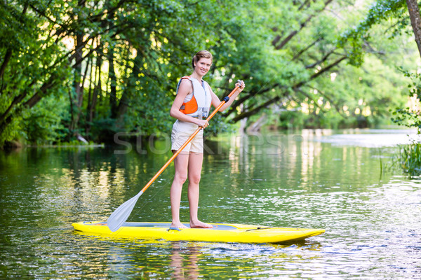 Woman paddling with surfboard sup on forest river Stock photo © Kzenon
