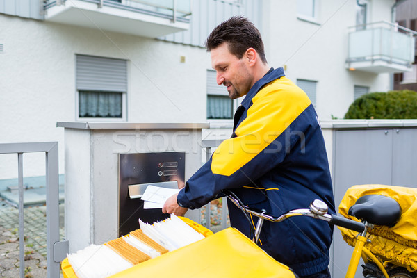 Postman delivering letters to mailbox of recipient Stock photo © Kzenon