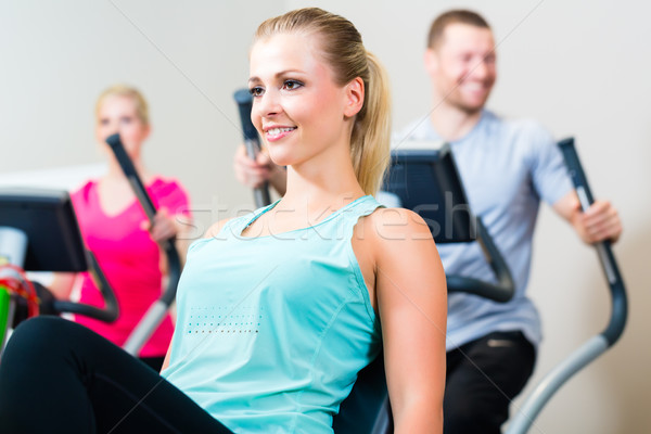 Group in gym spinning on sport bicycle Stock photo © Kzenon